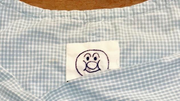 30年前に手作りしたチェック柄の子供用スモックの端にあるアンパンマンの刺繍